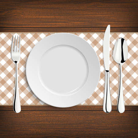 Plate with spoon, knife and fork on a wood table.