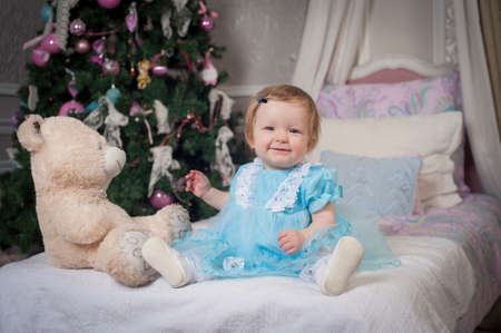 Little princess wearing a blue dress sitting on a bed Stockfoto