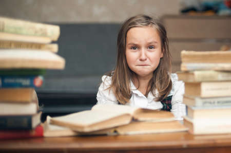 Girl in a school uniform sitting at a table Stockfoto