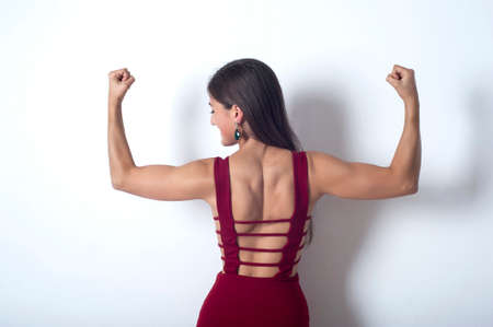 showing muscles: girl showing muscles in her arms Stock Photo