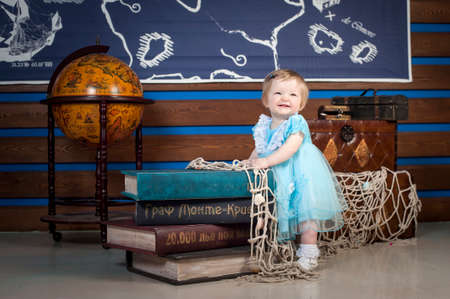 blue dress: baby in a blue dress with book and globe Stock Photo