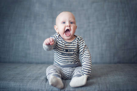 Very funny toddler sitting on the sofa