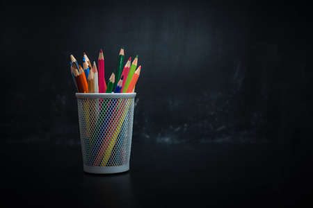 glass with colored pencils on black background blackboard chalk for drawing Stockfoto