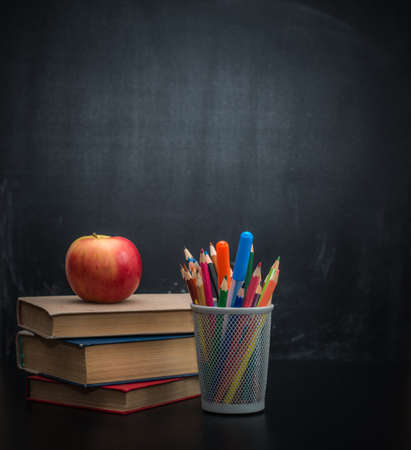 stack of books, cup of crayons and red apple against the black school board for chalk drawing