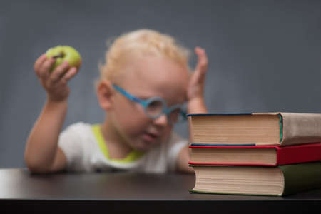 Child with glasses sits at a table with books and holding apple