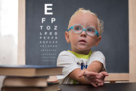 Child with glasses sits at a table in the background to check the table view
