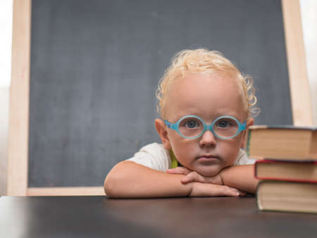 Child with glasses sits at a table