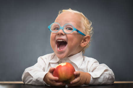 The child wears a white shirt sits at a table and eating an apple