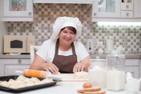 A girl wearing a kitchen apron and chef hat cooking cakes