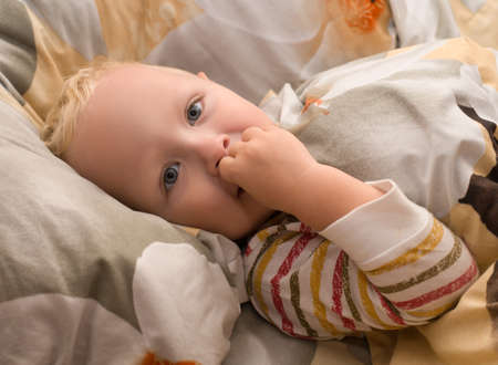 Smiling, happy baby lying in bed does not want to sleep Stockfoto