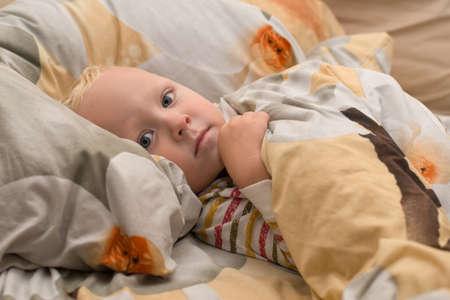 Sad sick baby lying on the bed