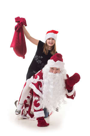 The child sits on the Russian Santa Claus and holding a bag with gifts
