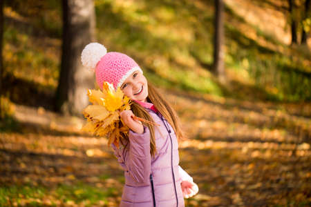 Happy baby girl wearing a pink hat is holding a bouquet of autumn leaves Stockfoto
