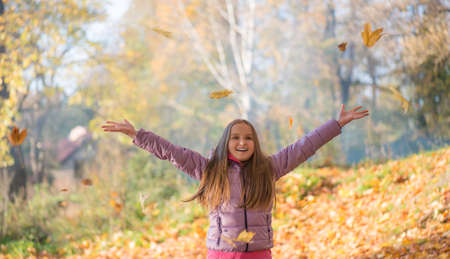 Happy baby girl throws up autumn leaves
