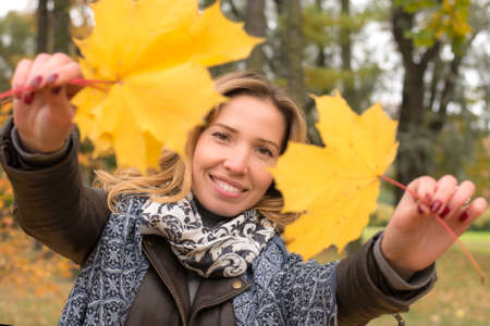 young girl laughing and holding autumn leaves