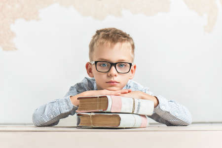 A dreamy schoolboy sits at a desk with books, wears glasses Stockfoto