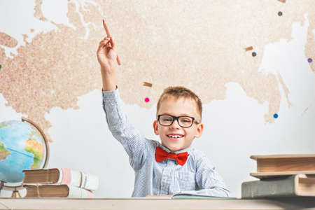 Emotional happy schoolboy wearing glasses, raised his hand up