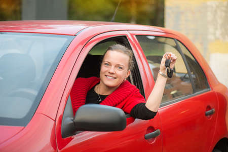 Red hair car smiles and holds car keys