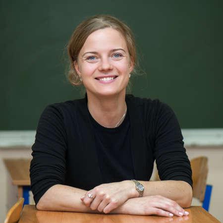 Student girl sitting on chalkboard