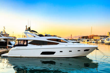 Luxury yacht docked in sea port at sunset. Motor boats and blue water. Relaxation and fashionable vacation.