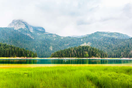 Mountains and Black Lake at cloudy daytime, Durmitor National Park, Zabljak, Montenegro. Beautiful nature landscape. Travel and vacation, tourist attraction. Stock Photo