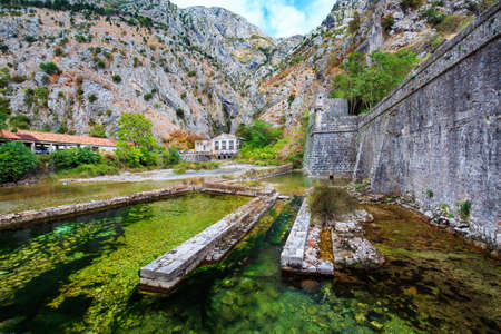 Mediterranean landscape. Overhanging cliffs, old power station near medieval city walls and river.