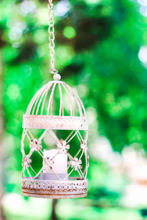 Vintage candle in decorative bird cage. Festive romantic decor, element of design, lamp and leaves, rustic details. White birdcage on floral background. Wedding decoration, green foliage and lantern.
