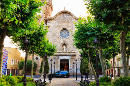 Old stone medieval Church of St Nicolau, it is known as the Cathedral of the Mediterranean Coast, Malgrat de Mar, Catalonia, Barcelona, ??Spain. Sidewalk, trees and street lights.