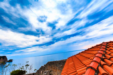 Wide angle view from the roof. Dramatic sky with storm clouds over sea. Birds eye view. Photo with a tilted horizon.