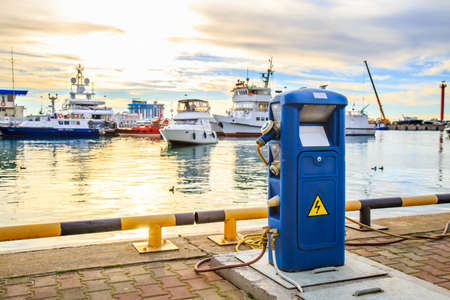 Charging station for boats, electric outlets to charge ships in harbor - supply of electricity for recharging of battery on shore in marina jetty. Electrical power sockets bollard point on pier near sea coast. Luxury yachts parking in port at sunset. Marine dock of modern motor and pleasure boats in sunshine, blue water. Travel and fashionable vacation.