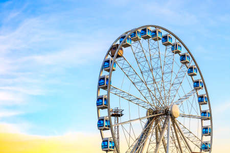 Ferris wheel on blue colorful sky background. Amusement park. Summer holidays and vacations. 写真素材