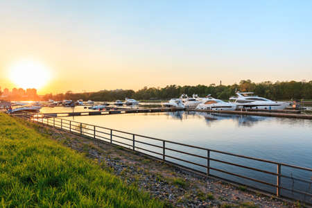 Luxury yachts docked in marina at colorful sunset. Marine parking, modern motor boats moored in water at pier. Summer view of Neva river bank, embankment and superyachts in sunshine. Sunny evening in St. Petersburg, Russia. Travel and fashionable vacation. Banco de Imagens