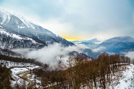 Foggy mountain landscape. Misty winter forest and valley. Fog at village, hiking. View of snow capped mountains and cloudy sky at sunset in Rosa Khutor, Krasnaya Polyana, Sochi, Russia. Stock Photo