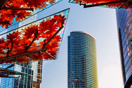 Skyscrapers in city street in Moscow, Russia. District of business and financial offices, modern buildings. Glass roof of bus stop. Orange maple leaves on awning or canopy, architectural details. Urban background, looking up, perspective skyline.
