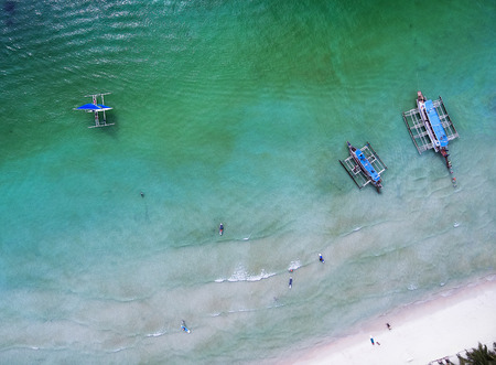 Aerial view of people landing on banca boats in the sea. Top view small beach with vacationing people, banca boats and paddleboard on a sunny day. View from above. Stock fotó