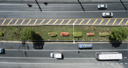 Aerial view of the wide road with a nice dividing strip of grass, flowers and trees. Top view of moving cars and buses. Flat illustration of road traffic. Stock fotó