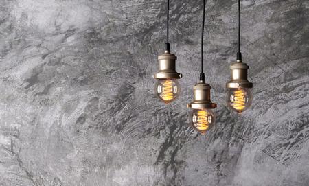Loft pendant lamps on the background of rough cement plaster on the wall. Minimal loftinterior. Edison light bulbs.