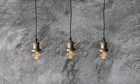 거친 시멘트 석고 벽의 배경에 로프트 펜 던 트 램프. 최소한의 실내 장식. 에디슨 전구.