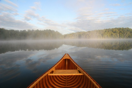 embark: Bow of a cedar canoe paddling on a northern Ontario lake