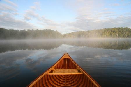 piragua: Proa de una canoa de cedro remando en un lago del norte de Ontario  Foto de archivo