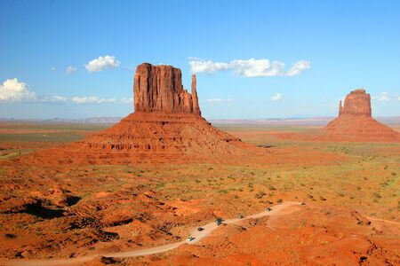 Left and Right Mittens in Monument Valley, Arizona dwarf the vehicles in the foreground Stock Photo - 8390020