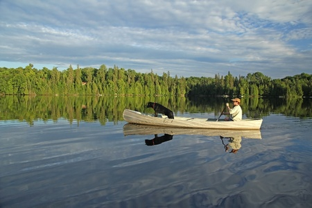 Man Paddling a Canoe on a Northern Ontario Lake with a Black Labrador Retriever in the Bow Stock Photo