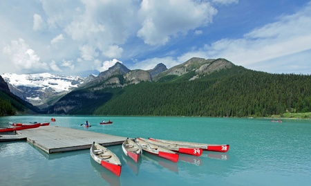 banff national park: Red Canoes on Lake Louise - Banff National Park, Alberta, Canada Stock Photo