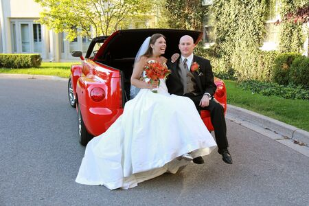 Bride and Groom Posing in a Red Convertible Truck photo