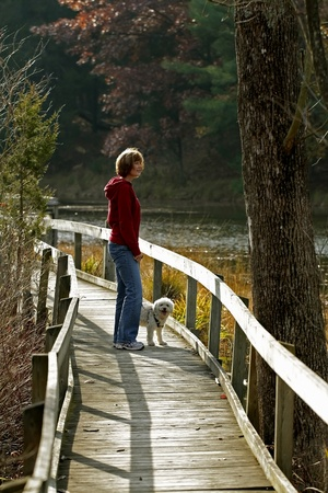 Woman and Dog Next to River on Boardwalk in Autumn 免版税图像