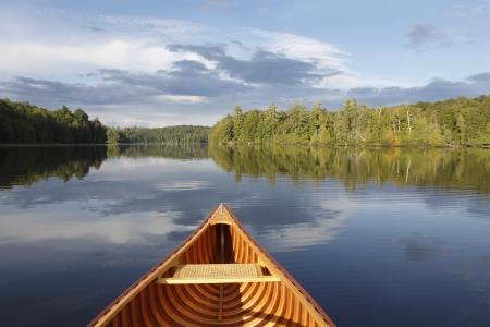 green boat: Bow of a Cedar Canoe on a Tranquil Lake - Ontario, Canada Stock Photo