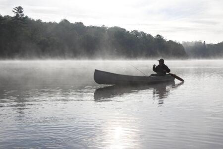 Fisherman Canoeing on a Misty Lake - Ontario, Canada photo