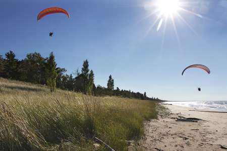 Two Motorized Hang Glider Kites Being Piloted Over Secluded Lake Huron Beach - Grand Bend, Ontario, Canada photo