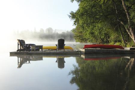 Dok met stoelen, Kano en Kayak op een mistige ochtend - Haliburton, Ontario, Canada