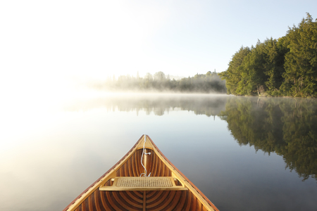 early summer: Cedar Canoe Bow on a Misty Lake - Ontario, Canada Stock Photo